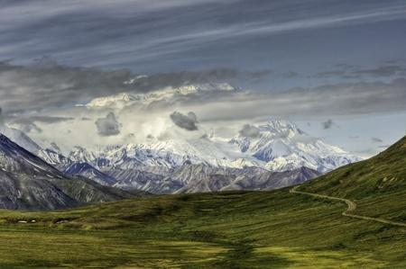 Mount McKinley peaks through dramatic clouds over lush green tundra in Denali National Park, Alaska. Stock Photo