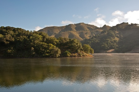 The morning light hits the rolling hills and chaparral of the central California on Uvas Reservoir. Stock Photo