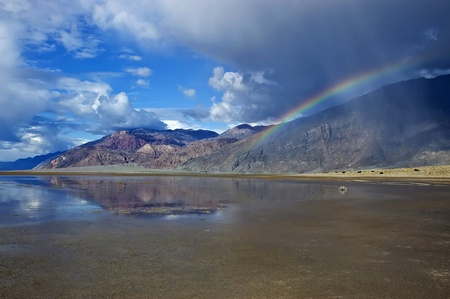 A rare cloudburst in Death Valley National Park yields a rainbow in badwater. Stock Photo