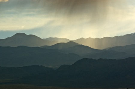 A cloud burst above a backlit mountainscape in Death Valley National Park, California.