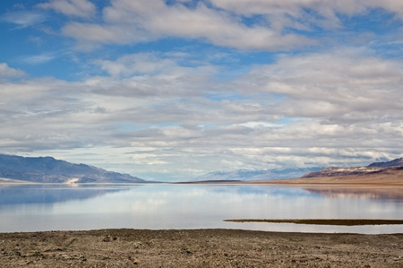 The mountains and sky reflect off the lake at Badwater, Death Valley National Park, California. Stock Photo
