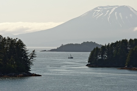 A boat fishes in Sitka Sound under Mount Edgecombe, Alaska. Stock Photo
