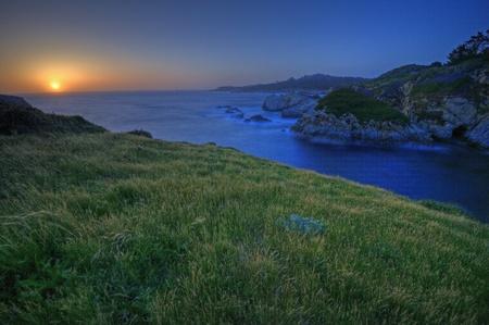 carmel: El sol pone en la accidentada costa Pacifc sobre una loma hierba por encima de la Ensenada de China en el punto Lobos estado preservar en Carmel, California.