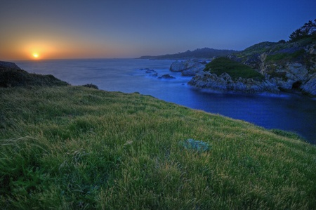 The sun sets on the rugged Pacifc coast on a grassy knoll above China Cove in Point Lobos State Preserve in Carmel, California.