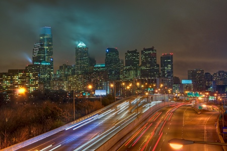 The Philadelphia, Pennsylvania skyline at night with the Schuykill Expressway in the foreground.
