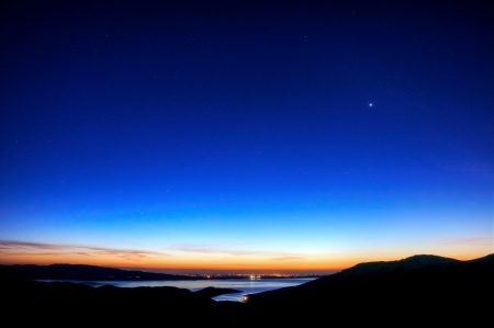 night sky: The sun rises on the San Luis Reservoir and Central Valley of California.