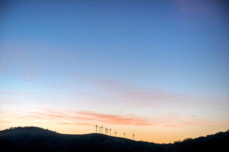 The sun rises on the wind turbines in the hills above San Luis Reservoir, California. Reklamní fotografie