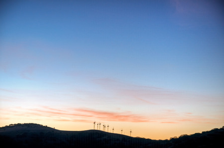 The sun rises on the wind turbines in the hills above San Luis Reservoir, California. Stock Photo