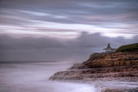 A gazebo in a cloudy sunrise along the Pacific coast, Santa Cruz, California. Stock Photo