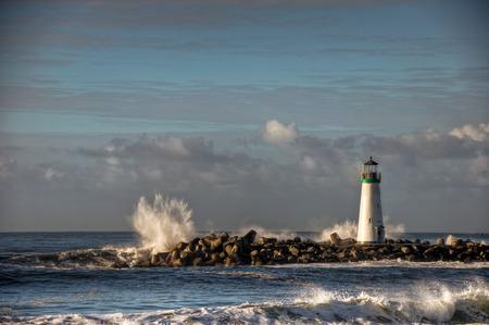 The waves pound on the rocks around the Santa Cruz Harbor Walton Lighthouse, California.