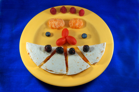A colorful lunch of peanut butter and apricot jelly on a tortilla with cherry tomatoes, blackberries, raspberries, blueberries and an orange on a yellow plate on a blue cloth.