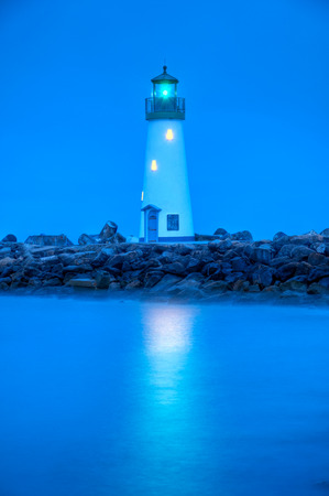 A pre-dawn blue view of the Santa Cruz Breakwater Lighthouse for the small craft harbor, Santa Cruz, California.