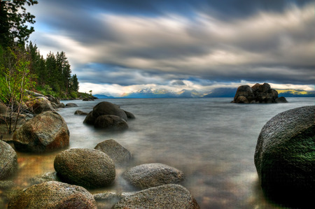 A long exposure of a stormy day on the rocky shoreline of Lake Tahoe