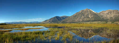A panorama of Jobs Peak and the surrounding mountains reflecting off of Carson Valley, Nevada