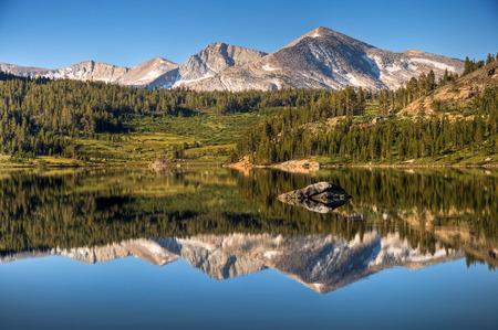 A reflection of Mammoth Peak and the Kuna Crest on Tioga Lake, Yosemite National Park, California  Stock Photo