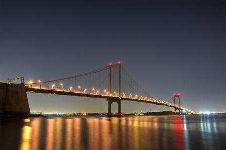 The Bronx-Whitestone Bridge reflecting on the East River at night in New York