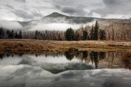 The reflection of Green Mountain on a pond in the East Boulder River valley in McLeod, Montana