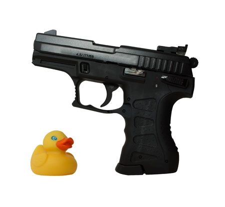 defenseless: defenseless duckling next to the aggressive pistol Stock Photo