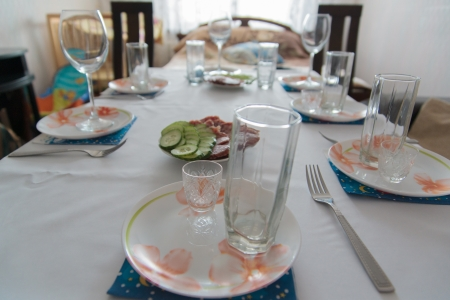 expects: Beautifully laid the table in the spacious room expects arrival of guests.