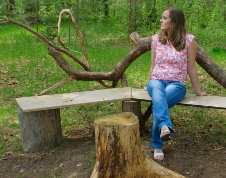 The young woman in a blouse and jeans sits on a bench in the wood photo