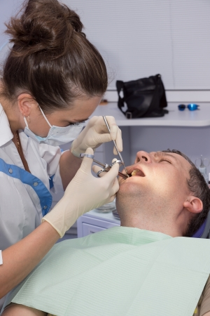 The doctor the dentist gives to the patient an injection for anesthesia before treatment  photo