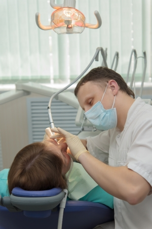 accepts: The doctor the dentist accepts the patient on the workplace in an office.