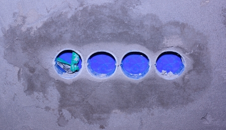 Four blue plastic nests for electric sockets are built in in a wall photo