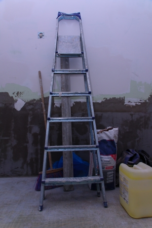 refinish: the step ladder and materials for repair stand near a wall Stock Photo
