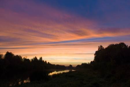 the sky is colored with different colors during sunrise over the river photo