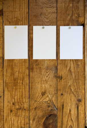 white sheets of paper attached to wooden wall with drawing pins photo