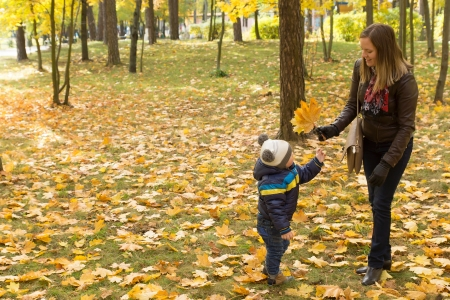 Mom and son playing with leaves in autumn park photo