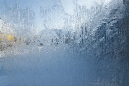 view of the street through the frozen window with frosty patterns Stock Photo