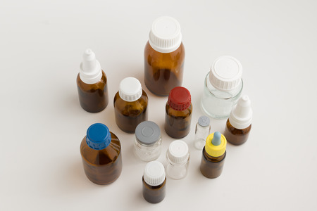 dispense: many medical bottles with caps on a white background