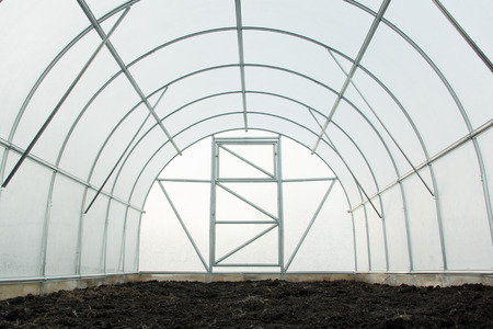 the greenhouse made of metal laths and transparent plastic Stock Photo
