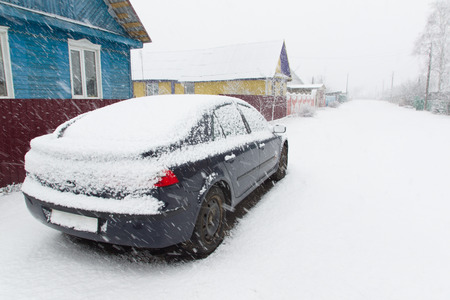 the blue car costs on the street under a heavy snowfall photo