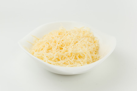 small grated cheese lies in a plate and is ready to use photo