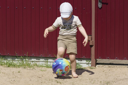 the little boy in a cap actively plays soccer photo