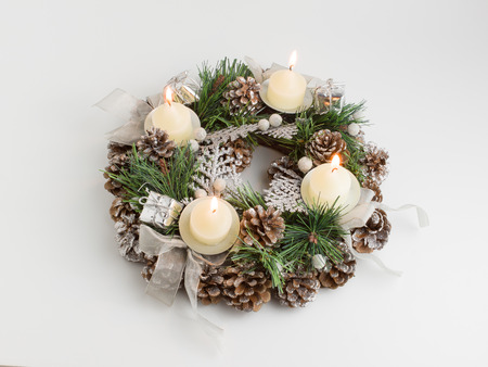 green Christmas wreath decorated with cones candles and bows photo