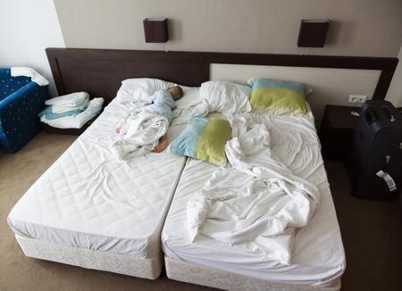 de kleine jongen slaapt in een hotel kamer op een groot bed Stockfoto