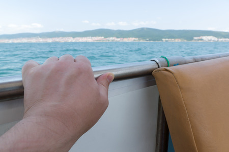 anja: the mans hand strong holds a hand-rail against the sea