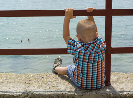banister: the little boy sits on a pier holds on to the banister and looks in water Stock Photo