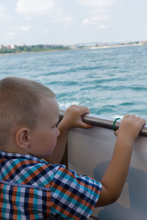 punting: the boy in a shirt costs at a board of a vessel and looks in a sea distance