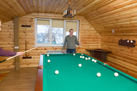 cue: the guy with a billiard cue expresses joyful emotions in a game anticipation Stock Photo