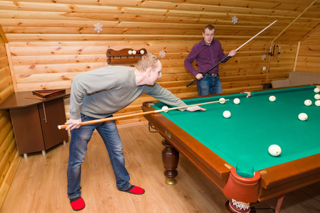 the guy with a billiard cue expresses joyful emotions in a game anticipation photo