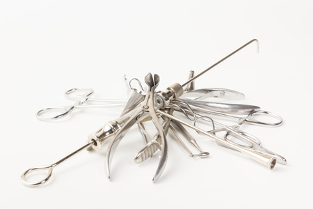 some chromeplated medical surgical tools lie on a white background photo