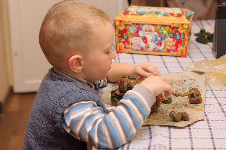 childs play clay: the little boy sits at a table and molds products from plasticine
