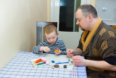 child's play clay: the father and the son sit at a table and are engaged in a molding from color plasticine Stock Photo