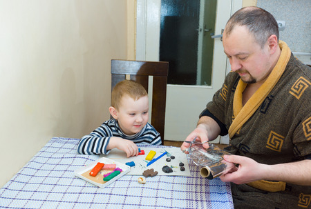 childs play clay: the father and the son sit at a table and are engaged in a molding from color plasticine Stock Photo