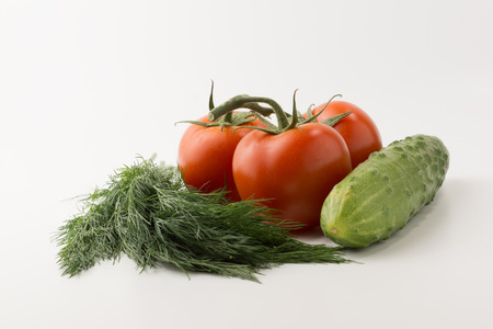 some small red tomatoes with a green branch and a cucumber with parsley and onions on a white background photo
