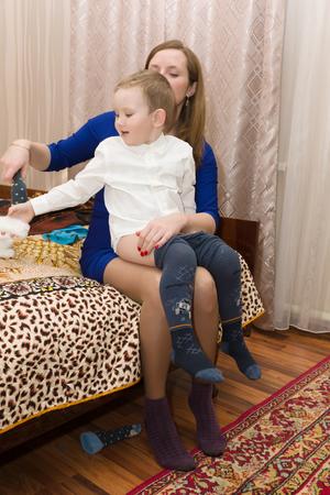 ni�os vistiendose: Mam� pone a su hijo en ropa de lujo listos para las vacaciones Foto de archivo